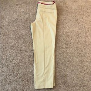 Beige ankle pants with hot pink belt